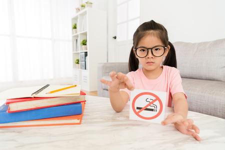 彼女は自宅のリビングルームで宿題を勉強しているとき、美しさエレガントな女の子は、カメラに禁煙の看板を示しています。