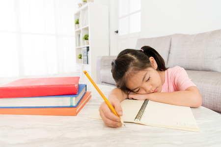 pretty young kid girl student leaning on living room desk sleep when she doing homework studying english textbook feeling tired.