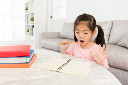 공부 하 고 많은 완료되지 않은 느낌이 그녀의 학교 숙제를 찾는 학교에 다시 준비 어린 아름 다운 소녀 충격을 받았다. 스톡 콘텐츠