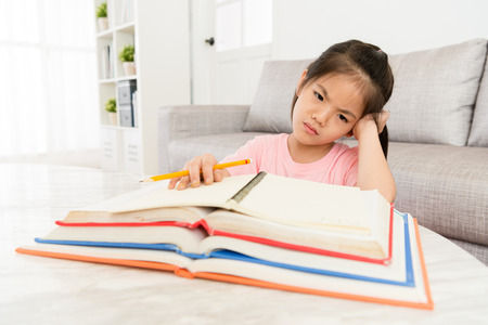 beauty attractive little girl looking at all homework feeling bored and unhappy when she preparing back to school studying. Banque d'images - 92349005