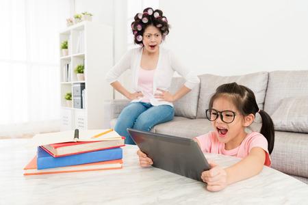 glückliche schöne kleine Tochter, die den beweglichen Auflagecomputer hält, der lustiges Video und ihre Mutter schaut, verärgert, sie betrachtend, weil Schulhausarbeit nicht beenden.