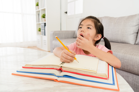cute young girl student writing school homework feeling tired sleepy and yawning want to rest.