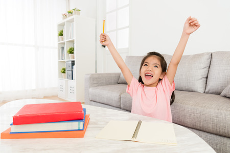 cheerful beauty girl kid raised hands up celebrating her school studying homework finally finished during holiday at home before back to school. Stok Fotoğraf