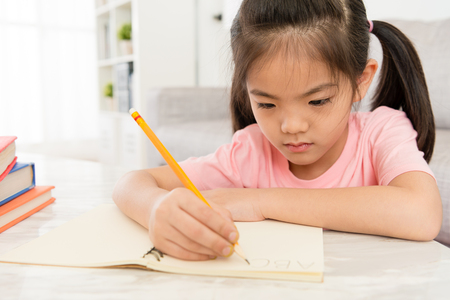 closeup photo of pretty attractive little female children doing homework at home and writing school book learning english ready back to school. Banco de Imagens