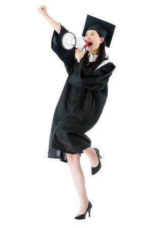 gelukkig mooie vrouwelijke afgestudeerde afgestudeerd college studeren op een witte achtergrond en het gebruik van luid megafoon praten te juichen vieren. Stockfoto