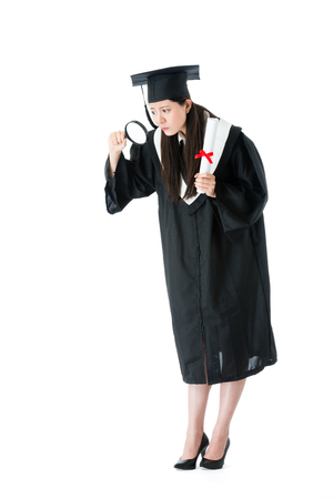 young attractive university female graduate standing on white background and using magnifier tool looking for future plan.