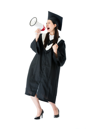 cheerful young female college student using megaphone announced she getting graduation diploma and celebrating on white background. Stock Photo
