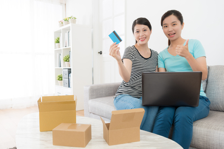 happy attractive women shopper face to camera showing thumb up when they using credit card paying online shopping at home. Stock Photo