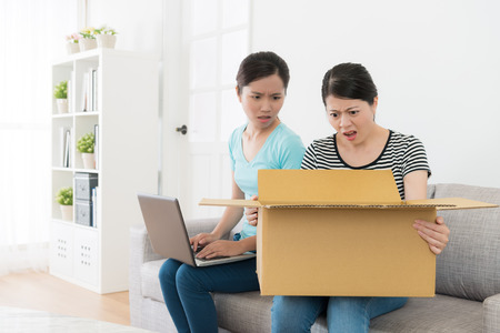 attractive beauty girls using online shopping website buying goods and received shipping box finding their parcel is wrong feeling confused. Stock Photo
