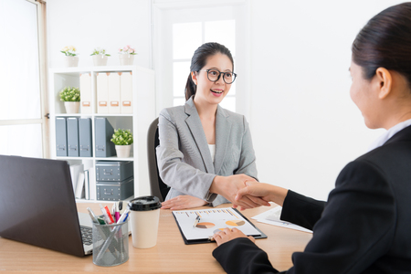 beautiful young business sales girl successful persuasion her client joining company cooperation case and hand shaking to celebrate. Stock Photo - 92705563