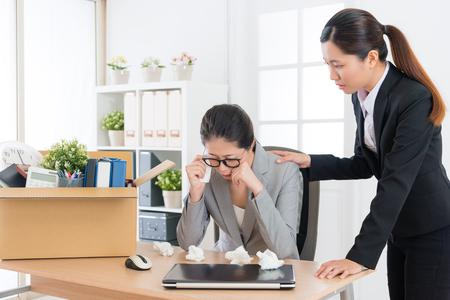 悲しいうつ病ビジネスウーマンは、オフィスで泣いてレイオフメッセージを取得し、かなりエレガントな会社の同僚の女の子は彼女を慰め。 写真素材