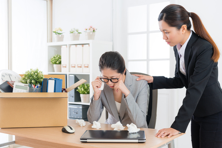 sad depression business woman getting layoff message crying in working office and pretty elegant company colleague girl consolation her. Stock Photo