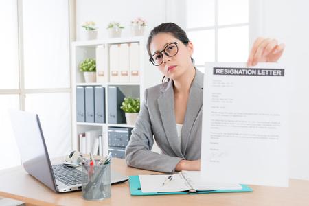 그녀는 새로운 직장을 변경하려면 회사를 떠나기로 결정했을 때 사임서를 보여주는 카메라를 찾고 전문 젊은 비즈니스 여자.