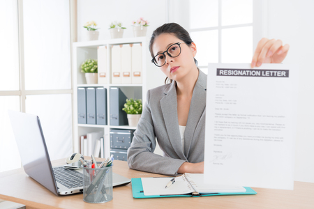 professional young business woman looking at camera showing resignation letter when she decided leaving company to change new job. Stock Photo