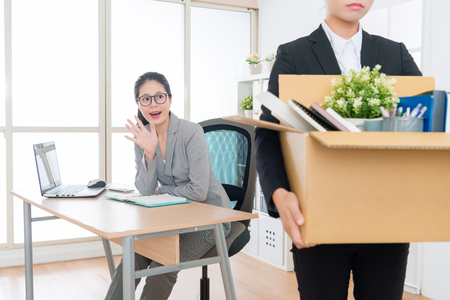 sadness young business woman losing job packing personal items box leaving company and her colleague feeling happy say goodbye.