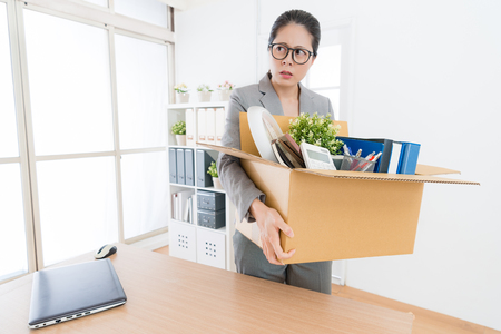 beautiful pretty office worker woman holding personal items box ready leaving company and feeling angry when she received layoff message. Фото со стока