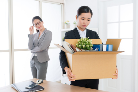 happy elegant company manager woman feeling cheerful when her colleague girl receives layoff message and ready leaving company.