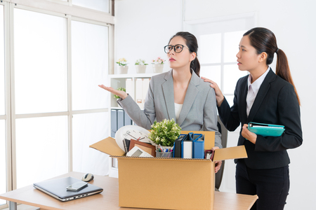 young beautiful business woman losing lob feeling confused and her colleague girl talking to console her when she packing personal items box.