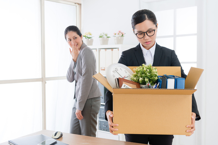 attractive beauty business girl holding personal belongings box ready to leave company and her colleague in back ridicule. Stok Fotoğraf