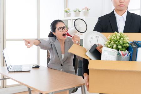 angry young business woman manager using megaphone shouting blame to office worker girl and fired her evicting leaving company.