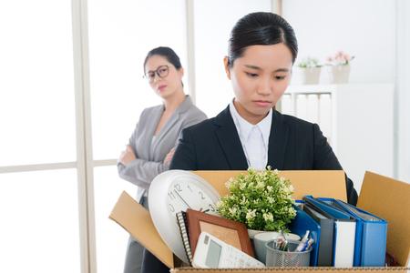 残す準備ができて個人的なアイテムを梱包会社の仕事を失う悲しいかわいいオフィスワーカーの女の子と彼女のマネージャーは彼女の幸せな気持ち