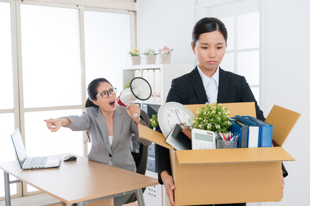 young beautiful business girl holding personal belongings box ready to leave company when angry mad boss woman using megaphone talking blame and fired her. Stock Photo
