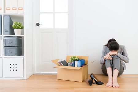 sadness pretty business manager woman unemployed sitting on wood floor crying with personal office items box.