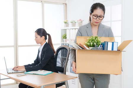 beautiful young business woman is fired and holding box leaving company.