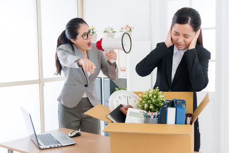 pretty attractive female boss speaking with young beauty girl business worker and using loudspeaker loudly shouting blame to fired her.