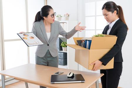 trabalhador de escritório da menina da beleza nova que perde o trabalho da empresa quando seu chefe que mostra o relatório de trabalho que sente insatisfeito e a demitiu.