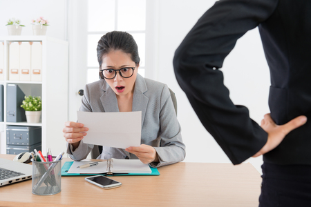 young attractive office worker woman getting fired feeling shocked when she received letter from her boss and looking at layoff message.