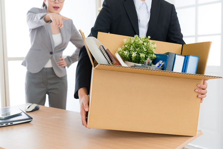 closeup of office worker employee girl holding personal box ready to leave company when angry boss woman blame and fired her.