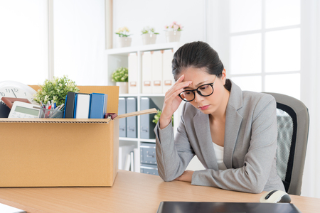 sadness pretty female office worker is fired packing personal belongings sitting on working desk feeling upset and thinking future job. Archivio Fotografico