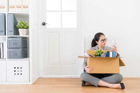 young beautiful business woman losing company job sitting on wood floor in white background with personal box and using mobile cell phone searching new work.