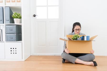 Mooie schoonheid vrouwelijke werknemer wordt ontslagen en bedrijf persoonlijke items vak zittend op bedrijf exit houten vloer huilen denken toekomst. Stockfoto - 92771824