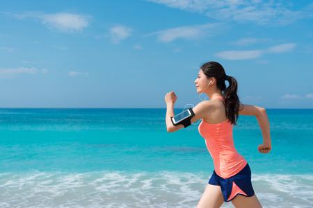 closeup photo of smiling happy girl traveler running on seaside enjoying beautiful landscape during summer vacation journey. Stock Photo - 92917715