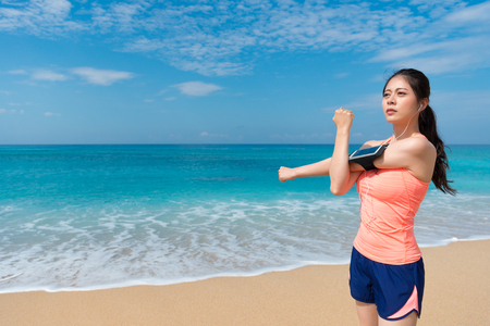 attractive young girl standing on seaside beach hands cross making arms warm up and wearing sports clothing ready to jogging.