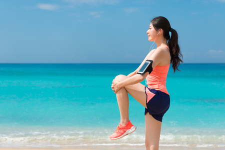 beauty young fitness runner woman doing warm up on beach before running and standing single to stretching knee when she going to beach travel. Stock Photo