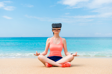 smiling beautiful fitness sporty girl wearing VR device sitting on beach and looking at 3D zen video to workout with lotus posture. Standard-Bild