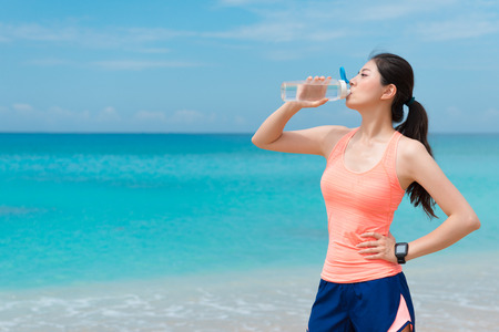 professional young woman athlete wearing smartwatch going to beach running and finished workout drinking water refreshing relaxing.