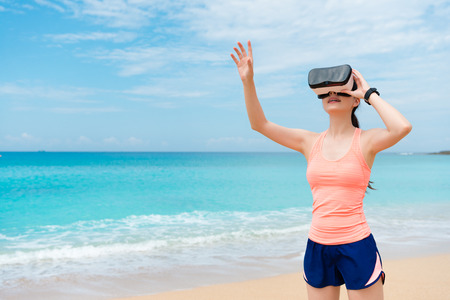 smiling beauty girl jogger wearing VR technology standing on beach and using hand touching simulation playing 3D video game relaxing.