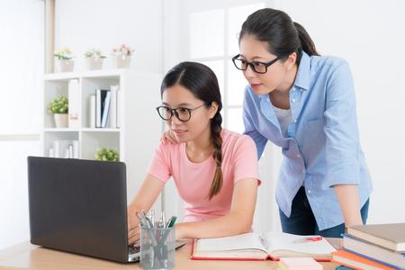 TUdiant jolie femme souriante à l'aide d'un ordinateur mobile fait ses devoirs à la maison avec l'enseignant étudiant et teste le résultat de l'apprentissage via le système e-learning en ligne. Banque d'images - 92870975