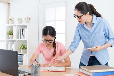 sad elegant girl student writing studying exam test book having problem feeling difficulty and home teacher pointing question reprimand her.