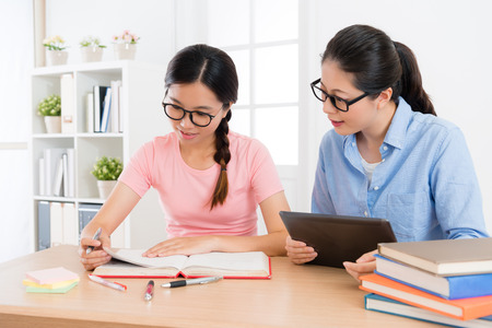 smiling elegant family teacher woman using mobile digital tablet to teach female student studying and preparing school exam. Stock Photo