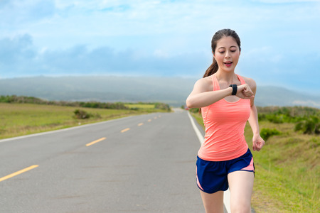 happy attractive girl runner using smartwatch system recording personal heart rate and confirm training route through GPS when she running on road workout. Stock Photo