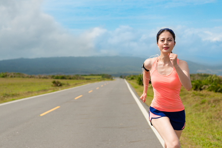 happy beautiful woman jogger running on road