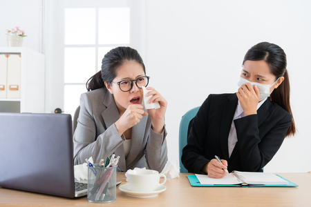 young pretty business woman wearing medical mask feeling fear when office worker manager sickness and coughing during meeting time.