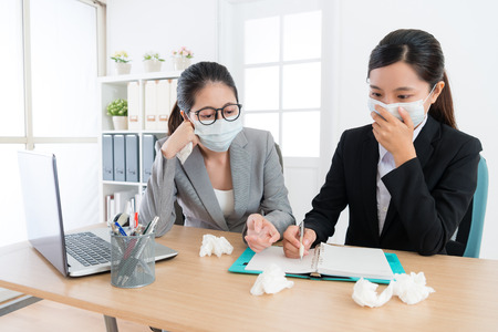 beautiful business woman having flu illness and wearing medical mask with co-worker to discussing company plan in order to avoid virus infection. Stockfoto