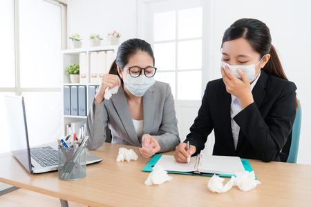 young pretty company female worker having teamwork meeting and wearing medical mask discussing together when one person catches cold.