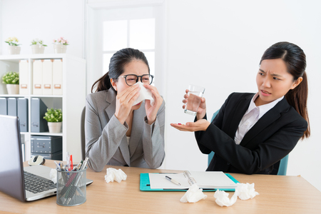 female business woman sneezing during conference and young pretty co-worker girl feeling fear giving medical pills for her.